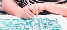 A close-up of artist Kara Bender's hands as she draws abstract green shapes on a piece of paper.
