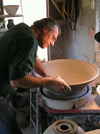 Jim Weber, a white man with grey hair wearing glasses and a green shirt, leans over the potter's wheel as he shapes a very large clay bowl. He is working in his home studio.