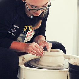 Christina Dixon, a white woman with long blonde hair in a braid, wearing glasses and a dark jacket with the Furman University logo, leans over a potter's wheel, carefully shaping a lump of clay into a vessel.