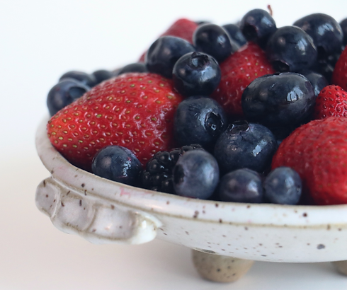 An assortment of berries sit in a speckled ceramic dish