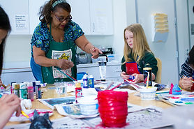 Mary Harris, an African-American woman wearing a blue patterned shirt and dark apron, assists a young female student with her project in SAM's art studio. The table is covered in bottles of paint, paper, brushes, paintings, and other art supplies for kids.