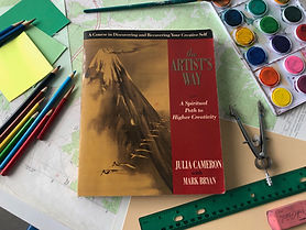 """A book titled """"The Artist's Way"""" lies on a table surrounded by markers, a pan of watercolors, paper, and pencils."""