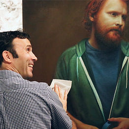 Diarmuid Kelly, a white man with dark hair wearing a grey shirt, smiles as he dusts off his large painting of a man with bright red hair and beard wearing a green hoodie.