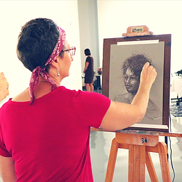 Kathleen Digney, a white woman with short grey hair, wears a pink shirt and hair scarf as she draws a pencil portrait of Brianna, an African-American woman, in the Museum. There are people milling in the background as she works.