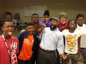 Instructor Moody Black, an African-American man wearing a white shirt, grey cap, and beard, makes a silly face with a group of students.