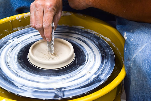 A hand holding a metal tool carves into a piece of clay on a potter's wheel