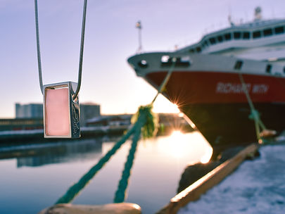 Northen Lights Necklace in Light Pink in front of a Hurtigruten Cruiseliner