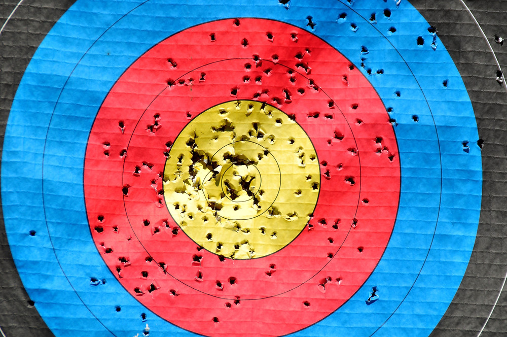An archery target is full of holes