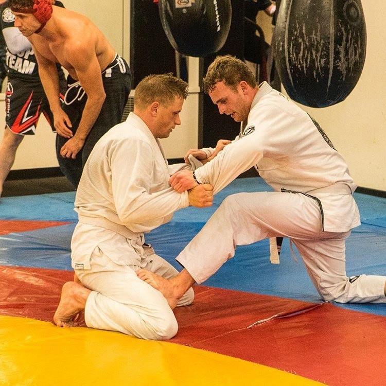 2 men practice Brazilian Jiu-Jitsu in a martial arts gym