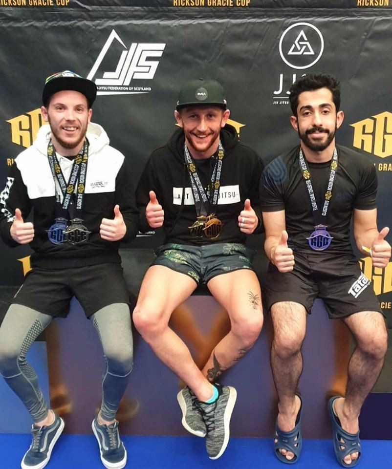 3 men wearing BJJ medals smile and pose for the camera