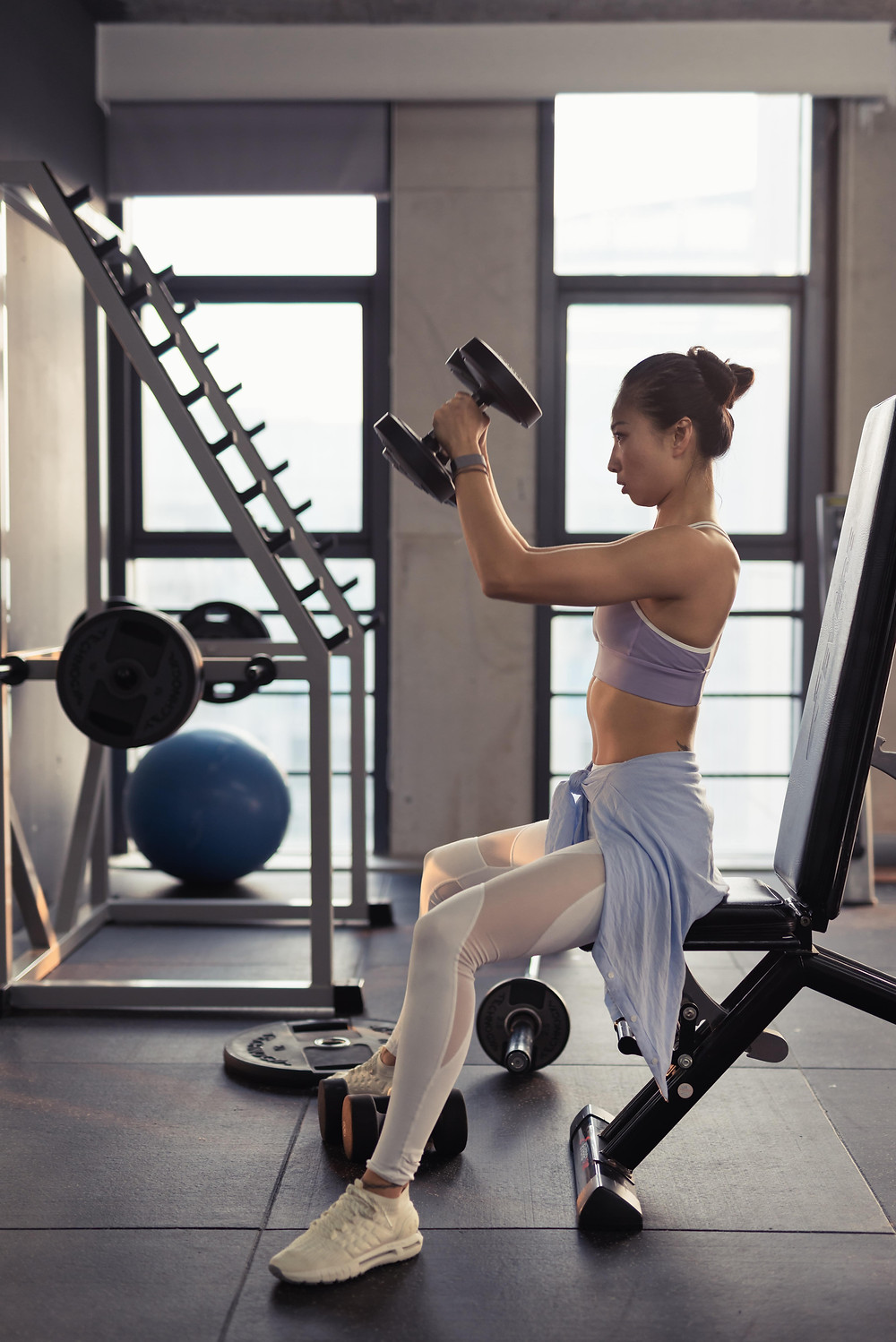 A woman lifts heavy weights in a gym