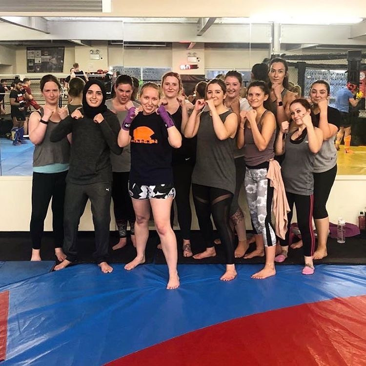 A group of women pose for a picture after a martial arts class