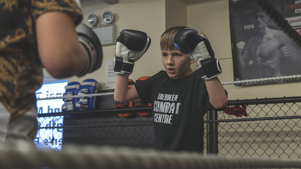A boy participates in Muay Thai in a boxing ring
