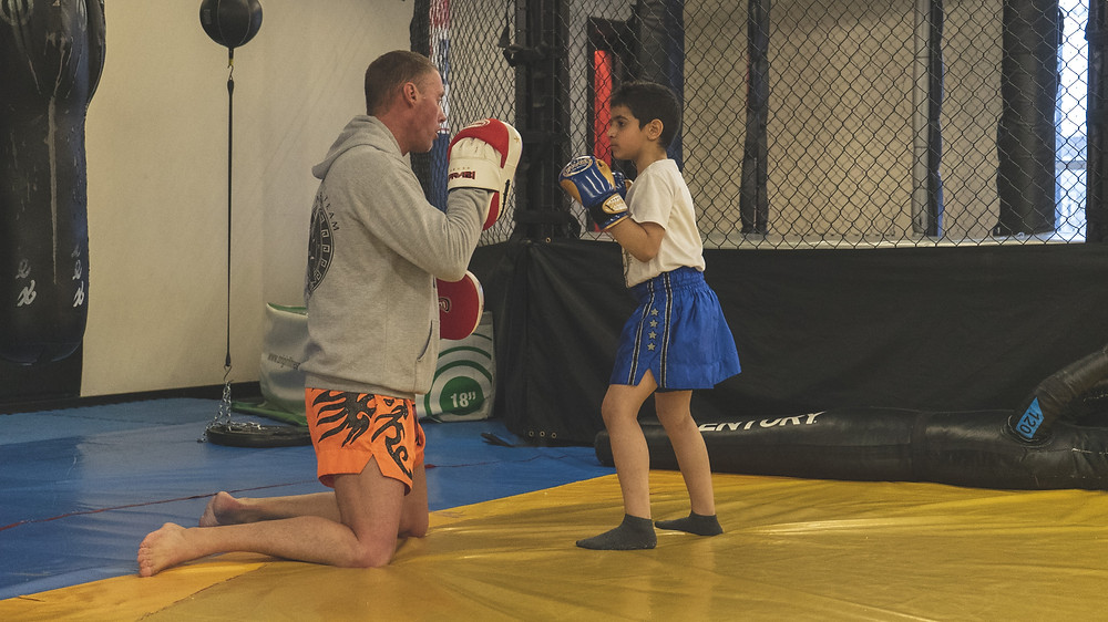 A young boy takes part in Muay Thai next to an MMA cage