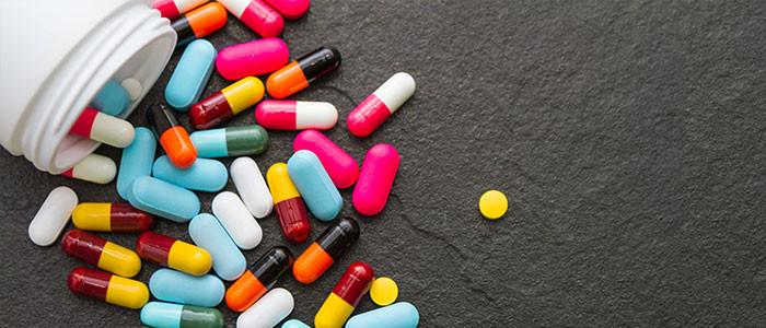 A open bottle of pills lie on a black surface
