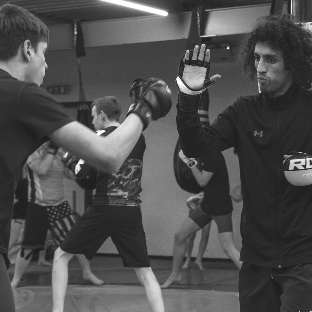An MMA class work on various technical drills