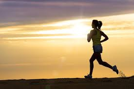 A woman runs with a sunset in the background