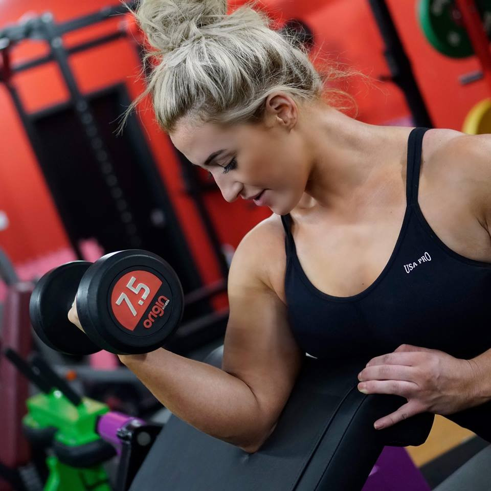 A woman lifts a dumbbell in a gym