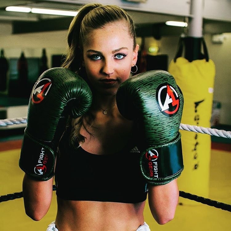 A woman wears a pair of boxing gloves in a boxing ring and looks at the camera