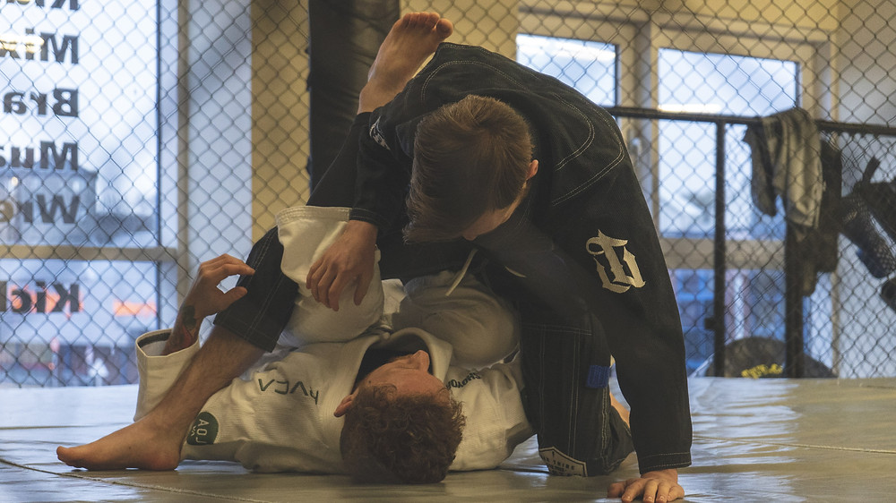 2 men in gi's take part in Brazilian Jiu-Jitsu in an MMA Cage.