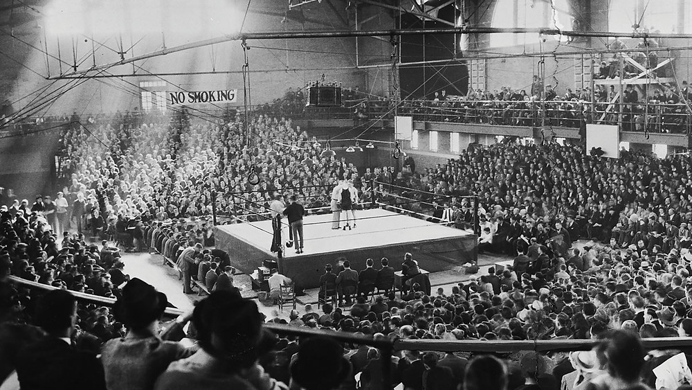 A stadium full of men watches a boxing match