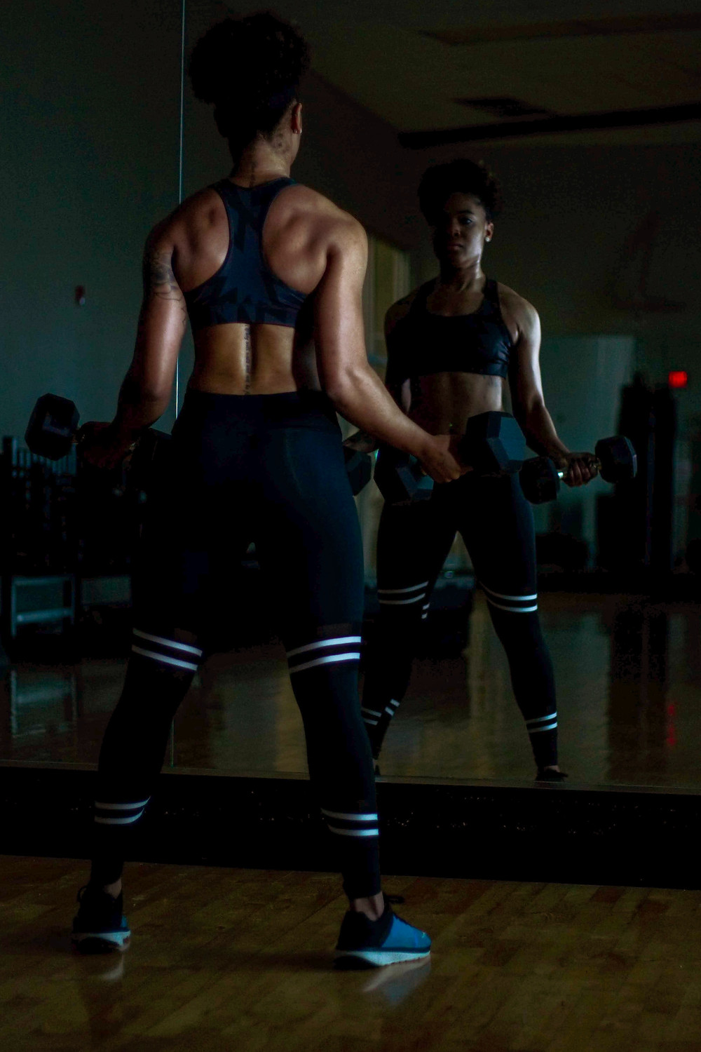 A woman lifts two dumbbells in front of a mirror