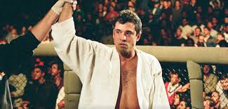Royce Gracie's arm is raised in an MMA cage