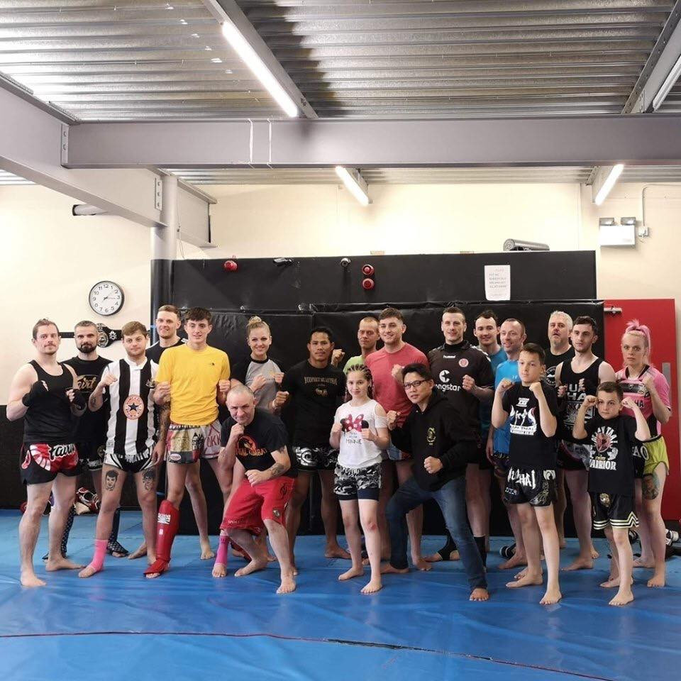 A group of adults pose for the camera in a martial arts gym