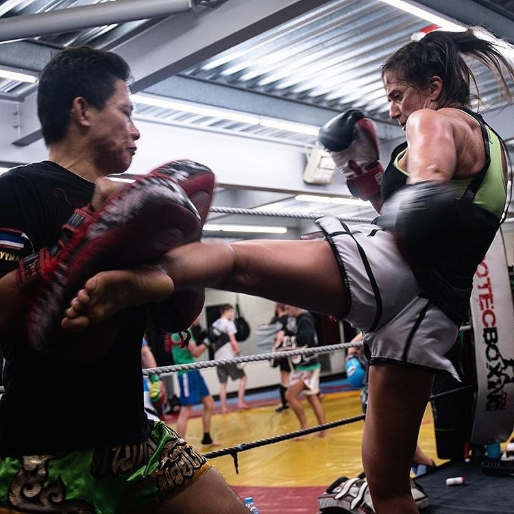 A women throws a Muay Thai kick at a man holding kickboxing pads