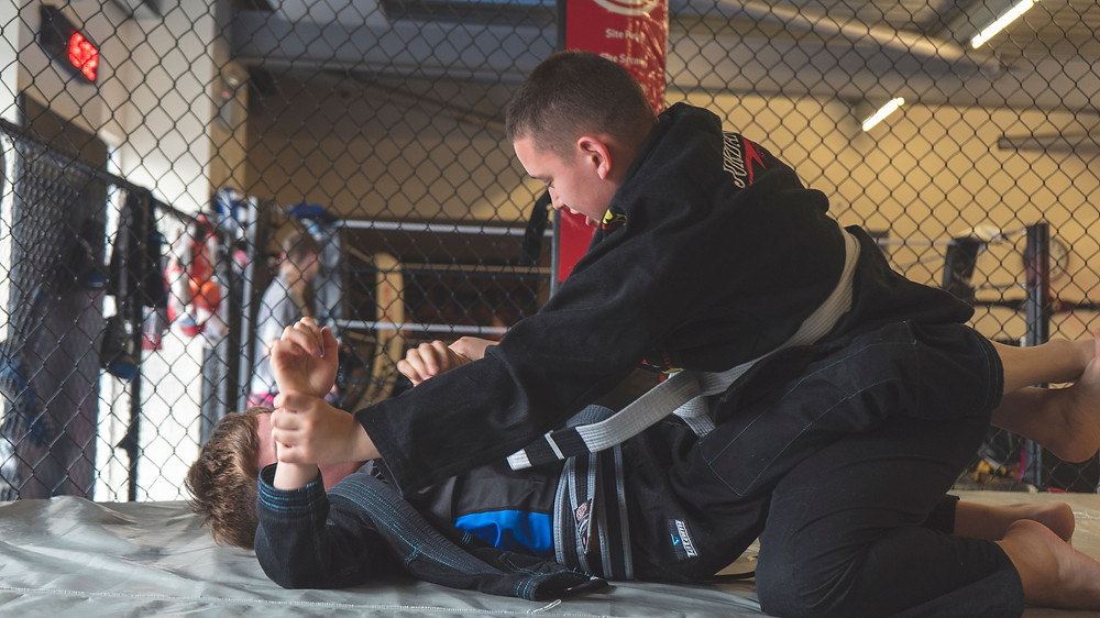 2 children take part in BJJ in an MMA cage