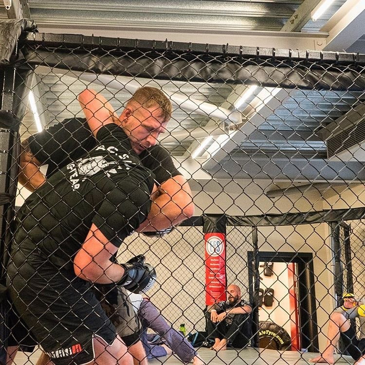 2 men wrestle against an MMA cage