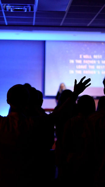 young woman raising hands during worship