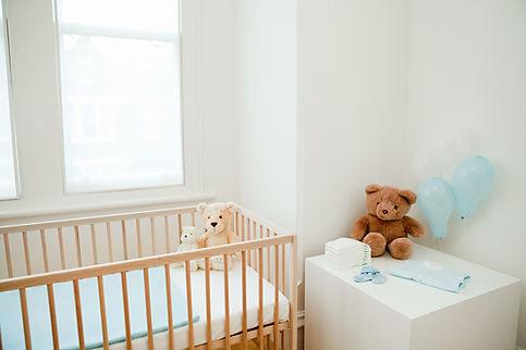 Babyzimmer mit Babybett-Teddybär und Kommode