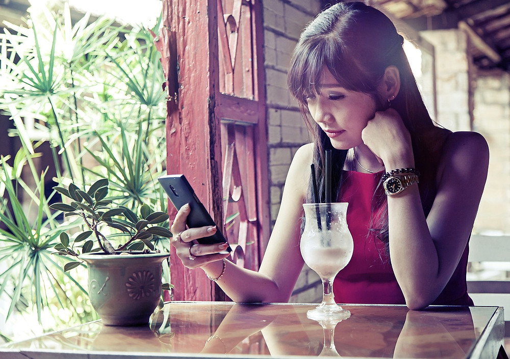 girl using mobile phone in a cozy place. pixabay.