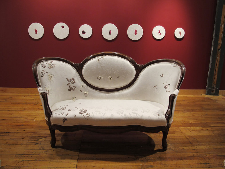 Own Your Cervis At Tangled Art Gallery, White Decorative Sofa in Front of  A Red Wall, Seven Circular Paintings Hang on The Red Wall, The Painting contain Splotches of Red Paint on A White Back Ground