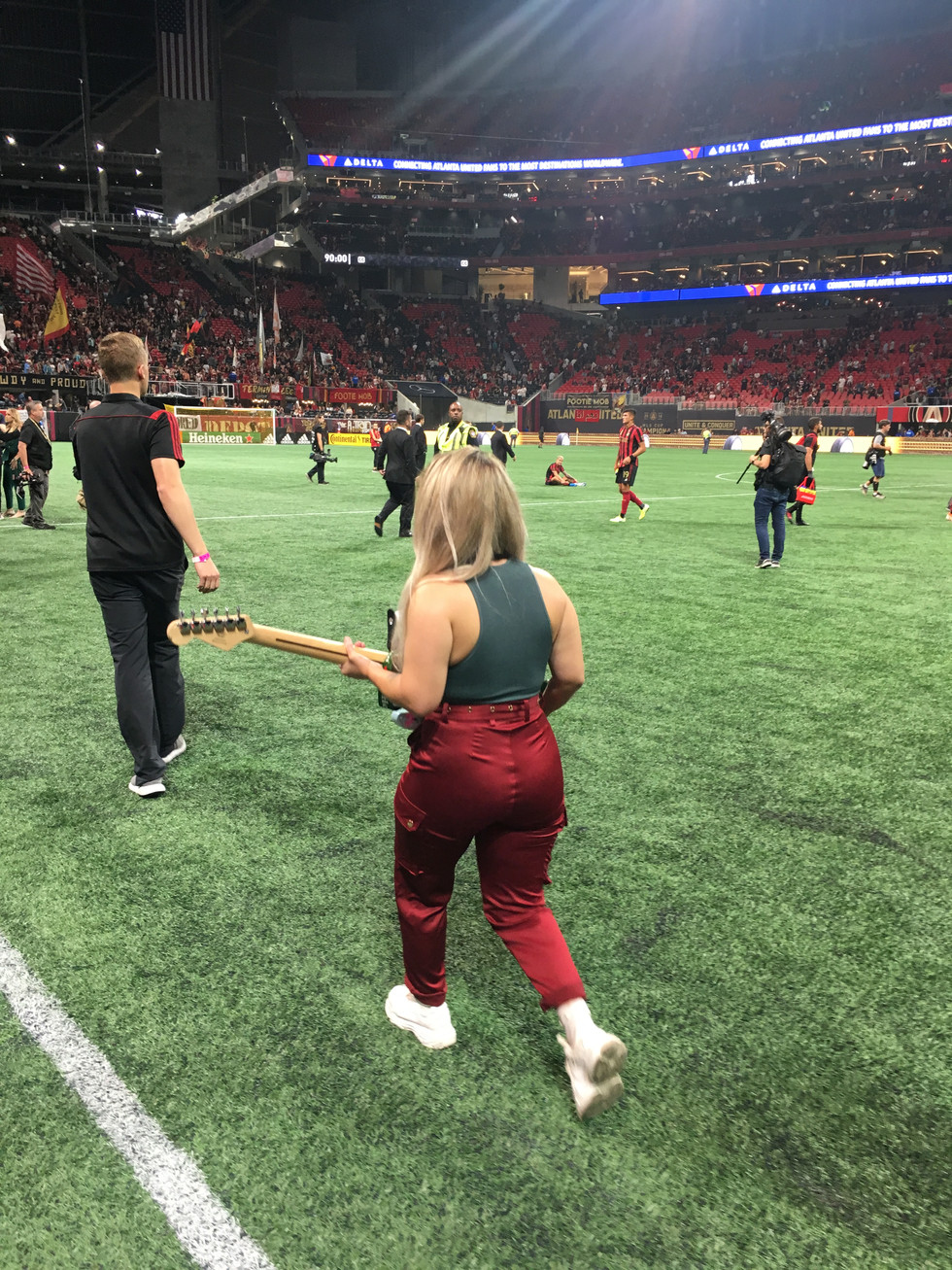 cathryn bozone at mercedez benz stadium delivering man of the match guitar