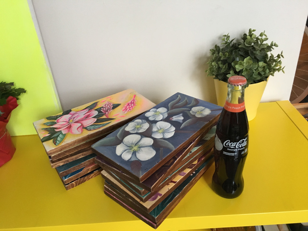 stack of paintings next to peach coke