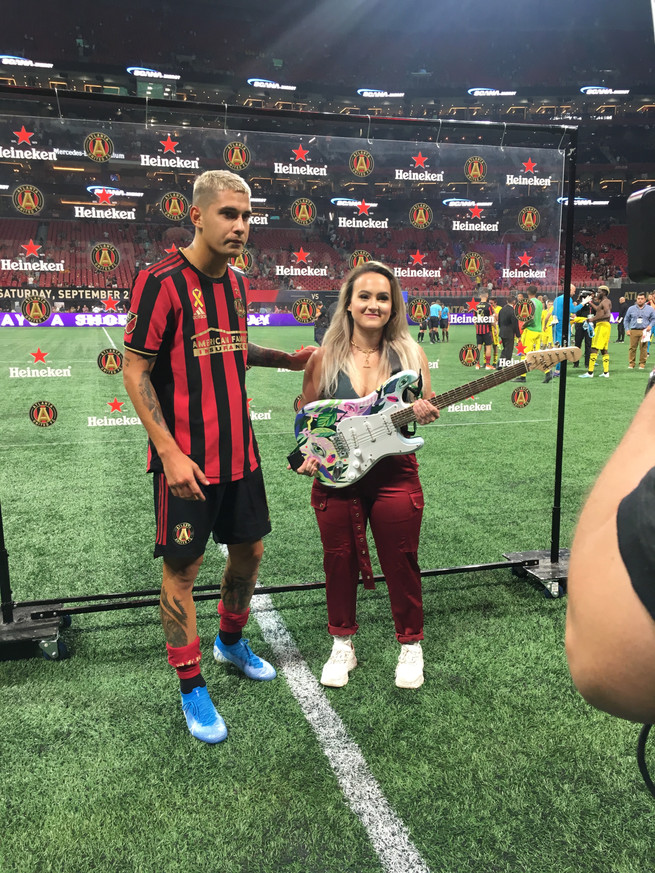 cathryn bozone delivering man of the match guitar at atlanta united game
