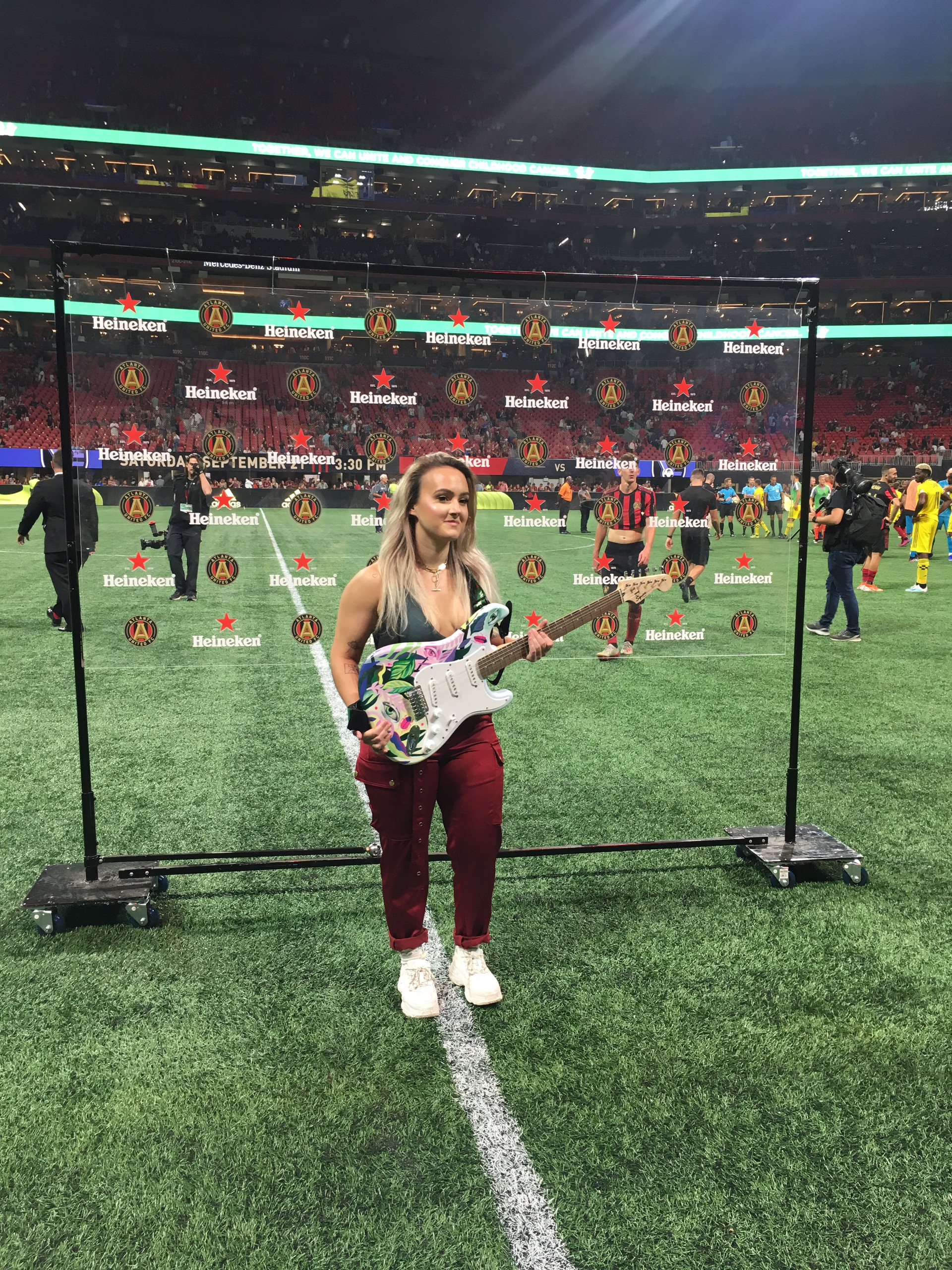 cathryn bozone at atlanta united game delivering man of the match guitar