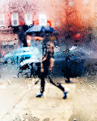 An image of a fogged up window with someone walking behind it.