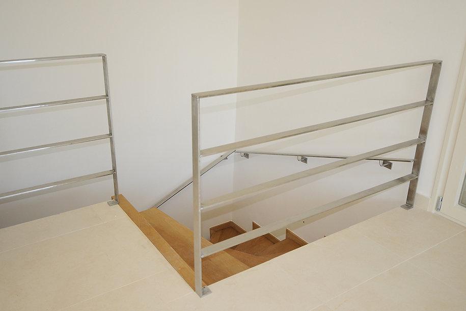 Λεπτομερεια εσωτερικης ξυλινης σκαλας με ανοξειδωτο καγκελο