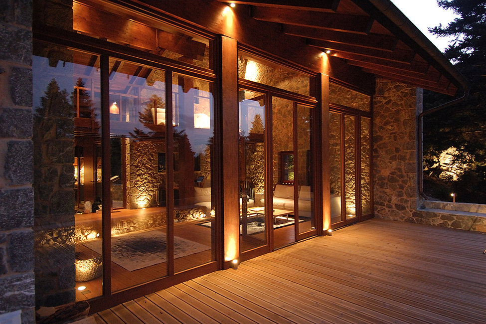 External night view of a balcony door and timber flooring