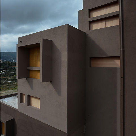 Modern brown stucco facade with rectangular openings