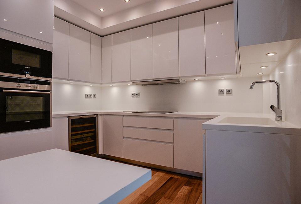 Ανακαινιση κουζινας με γυαλιστερες λευκες προσοψεις και ξυλινο πατωμα