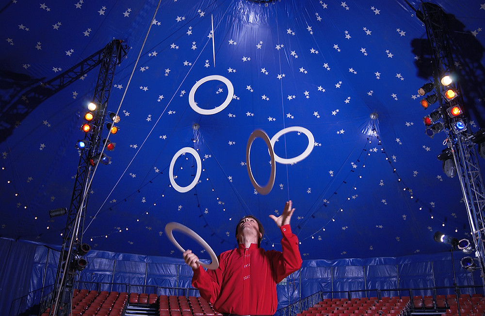 Juggler inside a circus tent performing.