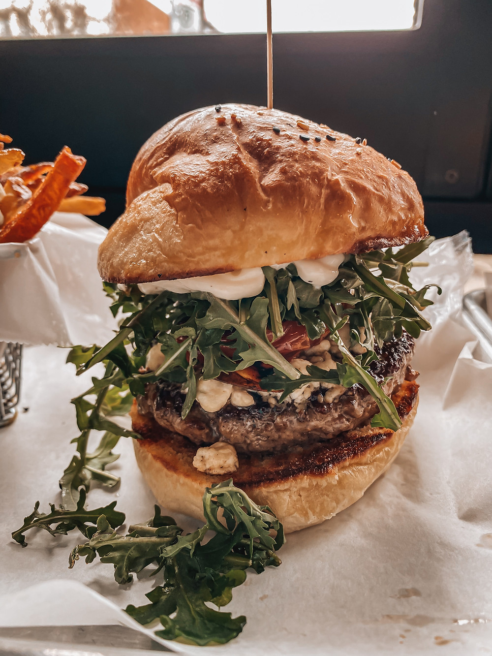 Beautiful burger with arugula, over-roasted tomato and goat cheese with truffle aioli