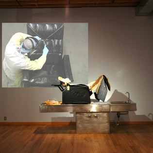 """Inanimate Autopsy (installation view Maryland Art Place), altered recliner, wood, stainless steel, and video projection H 5' 6"""" x W 8' 6"""" x D 2' 6"""""""