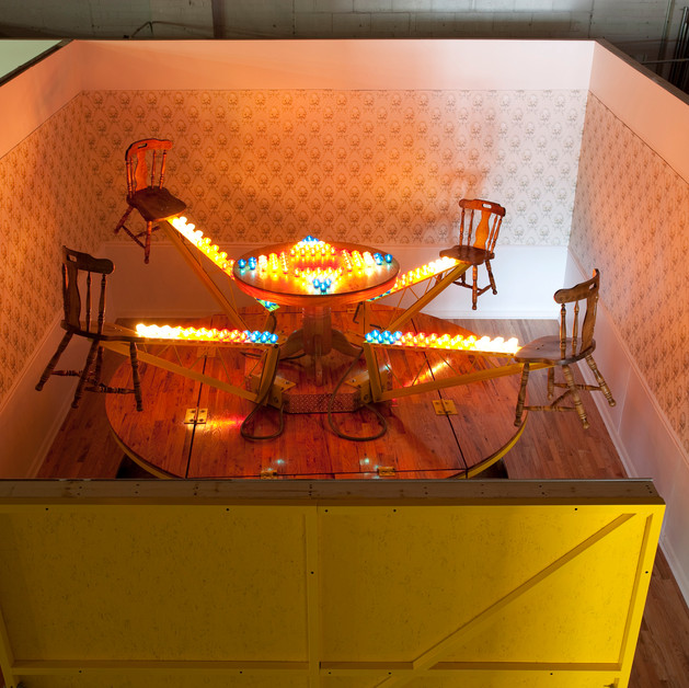 Domestic Carnival:  Dining Room (installation view Museum of Contemporary Art Detroit), Custom trailer, oak flooring, wallpaper, steel, altered dinette set, light chaser circuit and cabochon  carnival lights H 9' x L 16' x D 20'