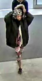 Woman stuffs home items under coat