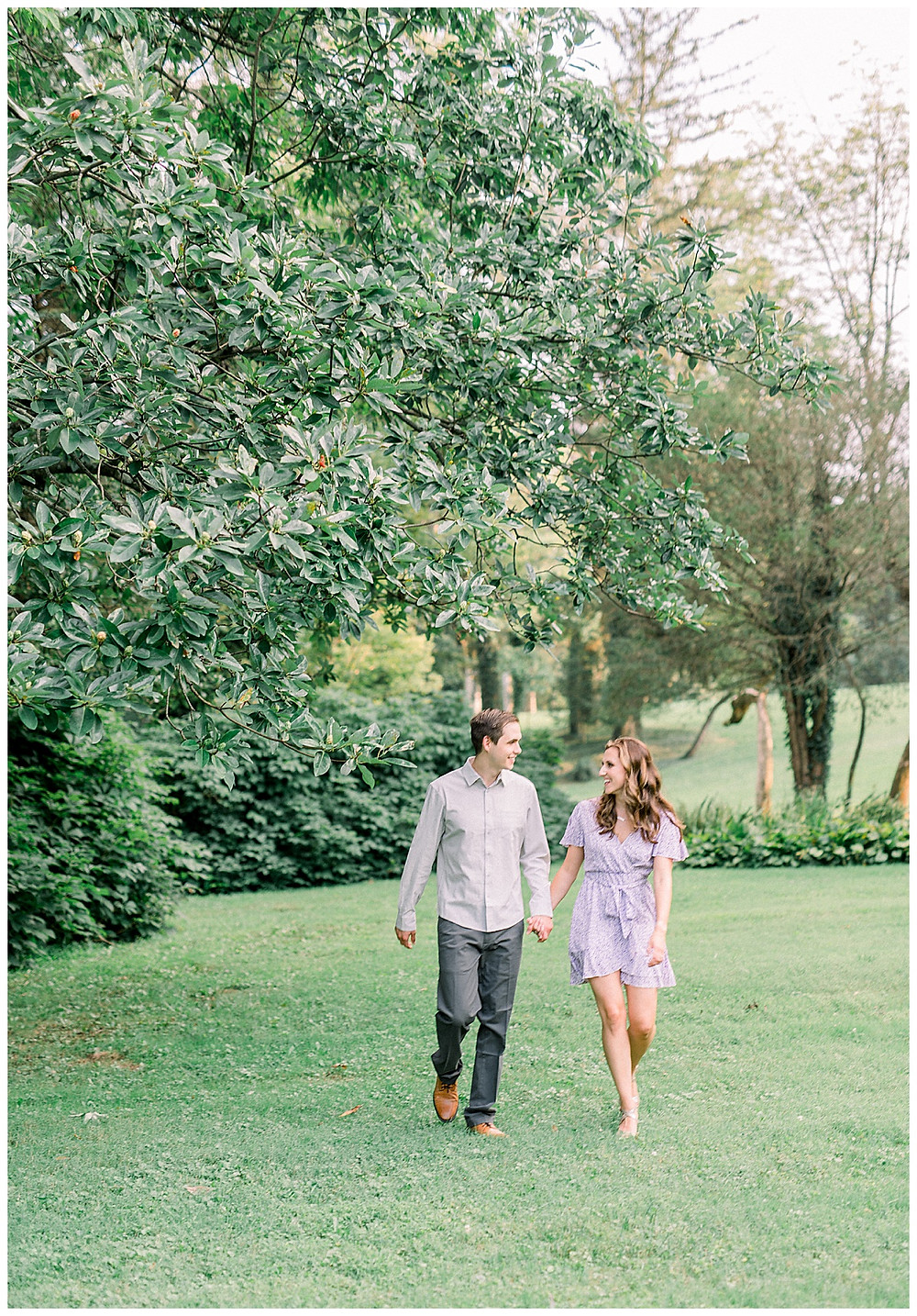An engaged couple holding hands and walking through Historic Shady Lane